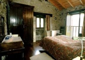 Dormitorio con cama de matrimonio y paredes de piedra