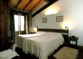 Habitación con dos camas individuales blancas y techo abuhardillado