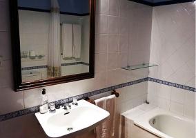 Cuarto de baño con azulejos blancos y espejo