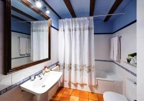 Cuarto de baño con vigas de madera en el techo