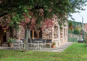 Detalle del jardín con mobiliario blanco y paredes de piedra