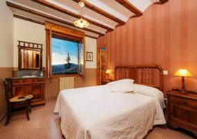 Dormitorio con una cama de matrimonio blanca y mobiliario de madera