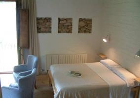 Dormitorio con cama doble y sillones