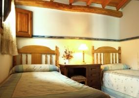 Habitación con camas separadas por un escritorio de madera