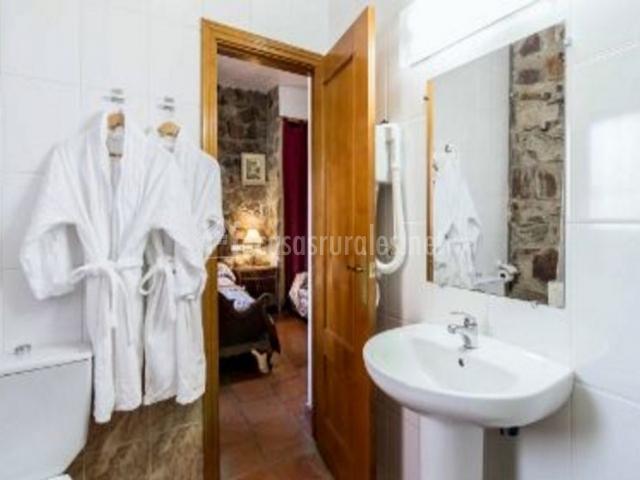 Dormitorio de matrimonio burdeos con vista del aseo