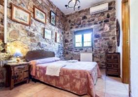 Dormitorio de matrimonio con paredes de piedra