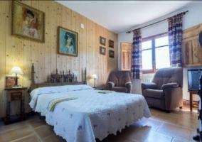 Dormitorio de matrimonio con ventana y pared de madera