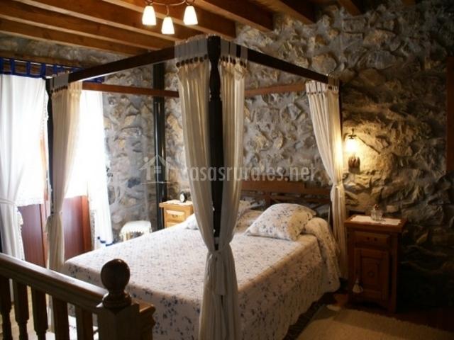 Habitación de matrimonio con paredes de piedra