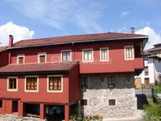 Acceso a la vivienda en tonos rojizos y piedra