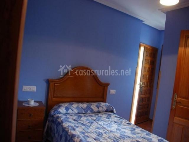 Dormitorio de matrimonio con predes de color azul y colcha
