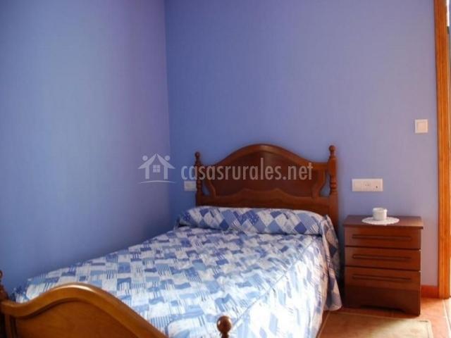 Dormitorio en color azul con mesilla y cabecero de madera