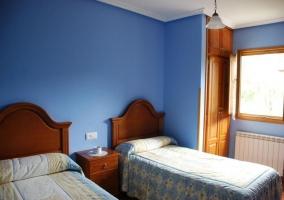 Dormitorio doble con paredes de color azul a juego con la ropa de cama