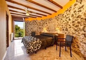 Dormitorio doble con pared de piedra y naranja