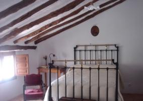 Cama de matrimonio en dormitorio con buhardilla