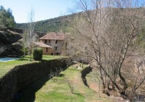 Vista general de la casa con la piscina y el rio