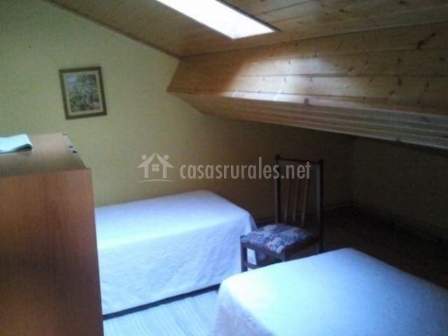 Dormitorio doble con techos de madera y un tragaluz