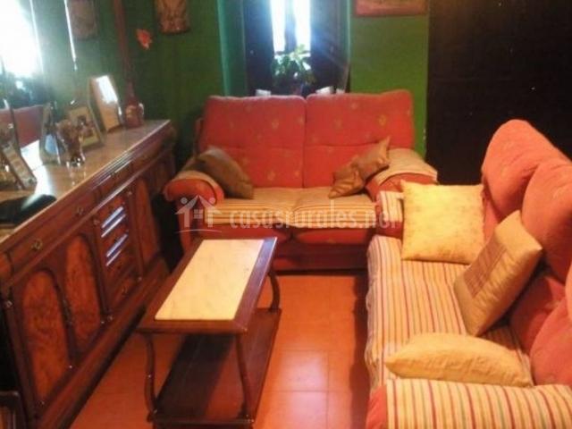 Sala de estar con paredes verdes y sillones en rojo