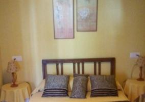 Dormitorio de matrimonio con mesillas y cojines