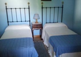 Dormitorio doble con mantas en color azul y cabeceros de forja
