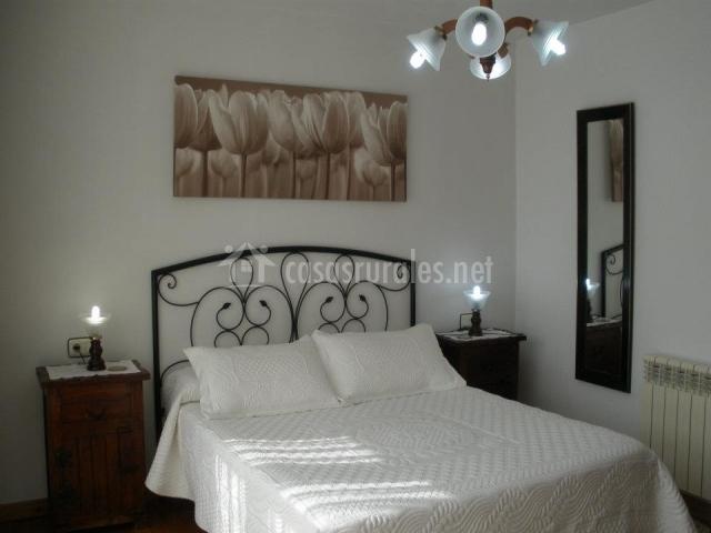 Cama de matrimonio blanca con decoración