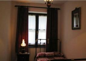Dormitorio individual con lámpara encendida