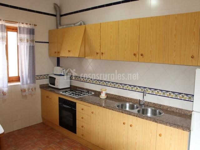Cocina independiente con muebles de madera y azulejos blancos