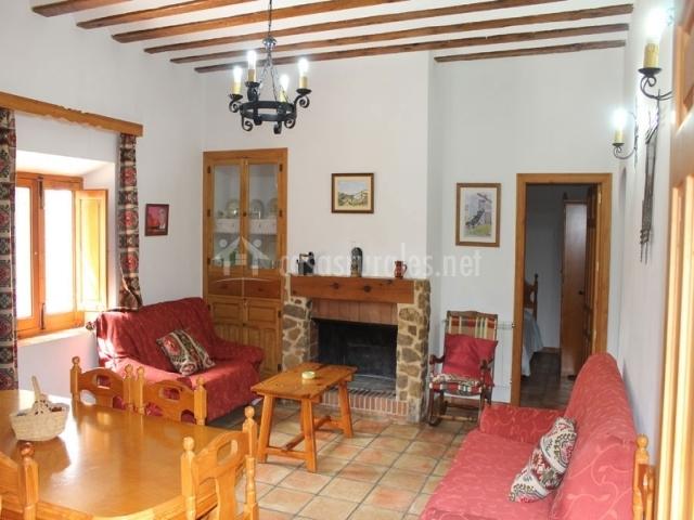Salón comedor con sofás rojos y mesa de madera
