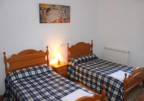 Habitación con dos camas individuales de edredon a cuadros blancos y azules