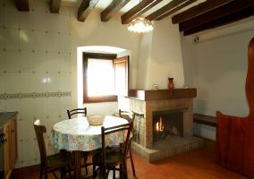 Mesa de comedor con sillas y chimenea en cocina