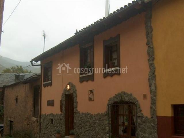 Fachada de la vivienda en color salmón y piedra