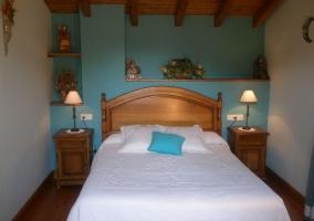 Dormitorio con gran cama y techo abuhardillado