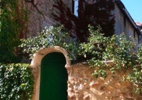 Entrada a la vivienda con muro de piedra