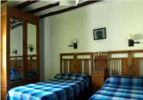 Dormitorio doble con colchas azules en casa rural