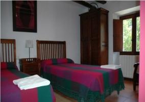 Dormitorio doble con colchas de colores  en casa rural