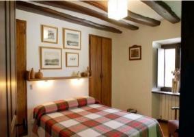 Dormitorio matrimonial con colcha de cuadros en casa rural