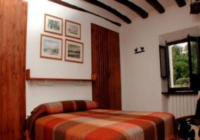 Dormitorio matrimonial en tonos ocres y rojizos en casa rural