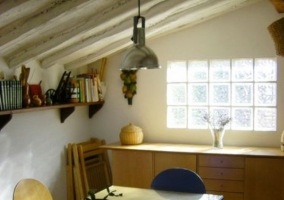 Mesa con sillas en el ático y techo abuhardillado