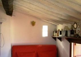 Sillón rojo con mobiliario y techo abuhardillado