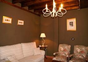 Sofá. sillones y techo de madera con vigas en el salón