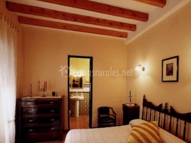 Dormitorio con cama de matrimonio con vigas de madera