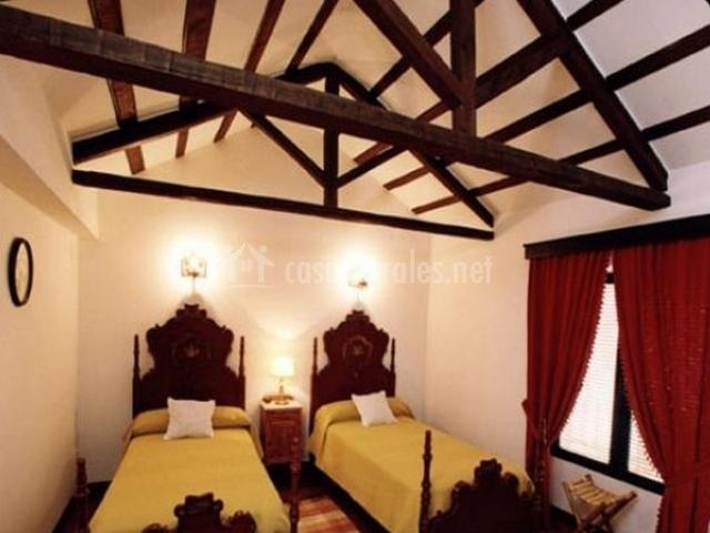 Dormitorio con camas individuales y vigas al aire