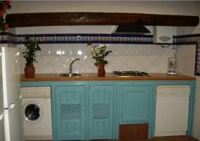 Cocina con azulejos blancos y muebles de madera azules