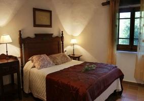 Dormitorio matrimonial con cabecero de madera y colchas bicolor