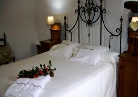 Dormitorio matrimonial con colcha blanca con cabecero de forja