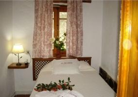 Dormitorio matrimonial con un pequeño cabecero de madera y mesita de noche