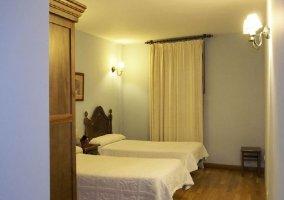 Dormitorio doble con colchas en color blanco y suelos de madera