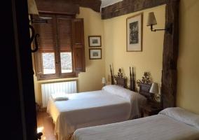 Dormitorio con dos camas y colchas de color blanco