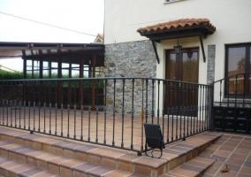 Entrada y terraza cubierta con muebles de exterior