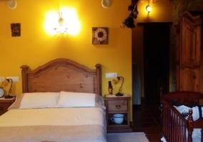 Dormitorio de matrimonio con colchas de tonos crudo y cuna