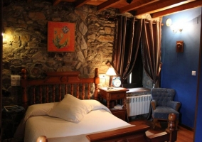 Dormitorio de matrimonio con paredes aazules y de piedra